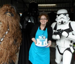 Baker Natalie Porter holding a Star Wars-themed cake, flanked by a Storm Trooper and wookie