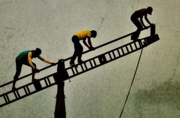 three people climbing the arm of a crane