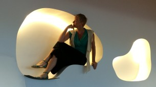 Woman poses in a one-person wall pod at Basketball court at new GoDaddy Global Technology Center in Arizona