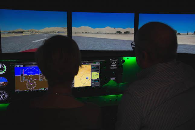 Aerodyne Flight Center co-founder Doug Cox, right, teaches the author some aviation basics in the Redbird Flight Simulator.