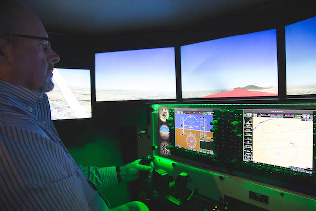 In the coxpit: Doug Cox takes the yoke in a flight simulator with a sophisticated GPS that generates real-time, geo-specific imagery.