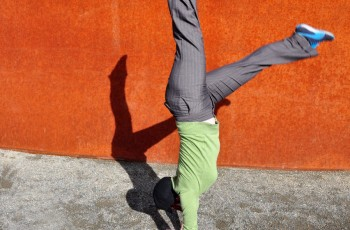 person doing handstand against orange wall
