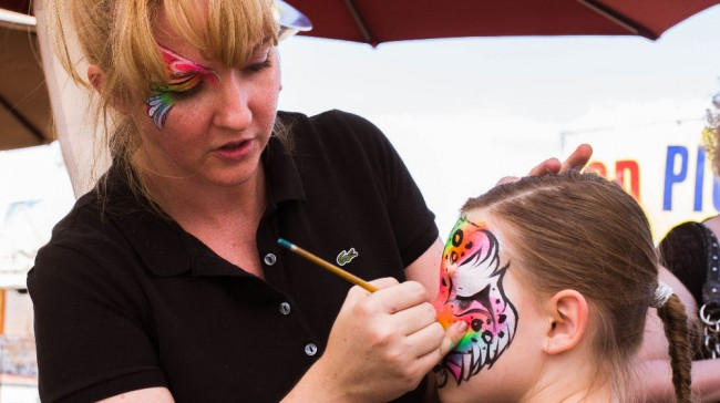 dianne nowicki of hello face paint painting a design on girl's face