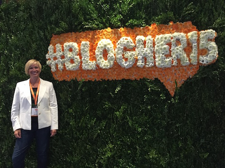 Andrea Rowland in front of #BlogHer15 floral sign at conference