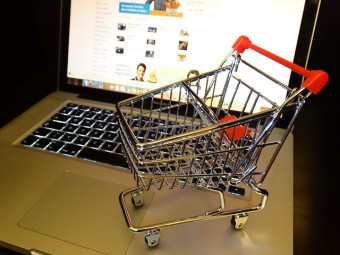 miniature shopping cart on keyboard to represent holiday sales tips for ecommerce websites