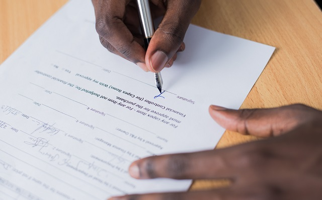 Person Signing Contract Demonstrating How To Get A Business Line Of Credit