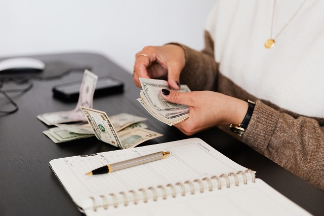 Woman Counting Money At Desk