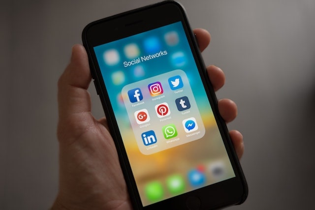 Person holding smartphone with social network icons