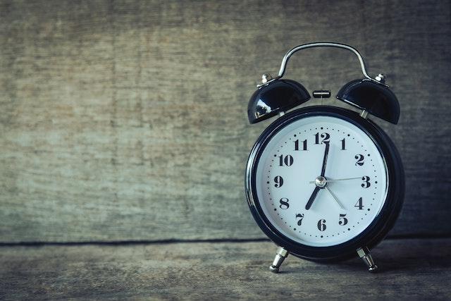 Black analog clock on wood background