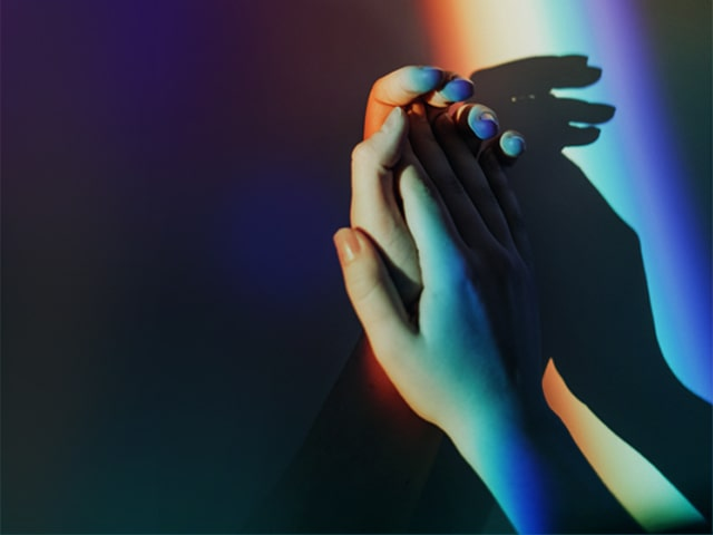 Hand together with rainbow light