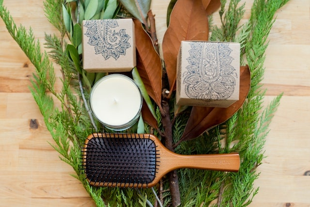 Brush and candle on table with greenery