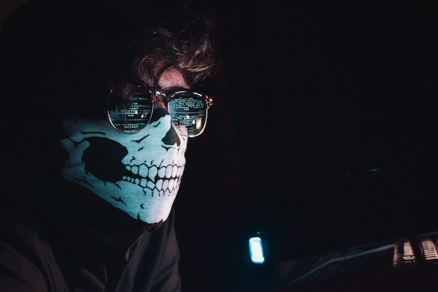 hacker sitting at computer with mask and glasses