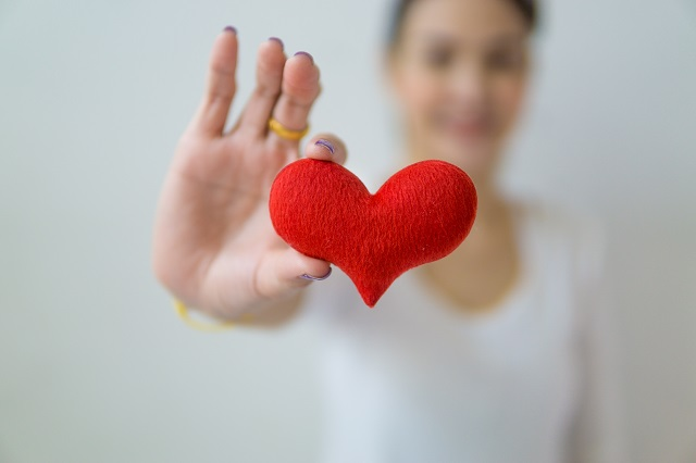 Woman holding red felt heart