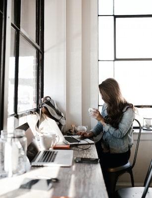 Woman blogging at coffee shop]