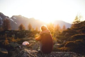Woman sitting in mountains looking at sunset