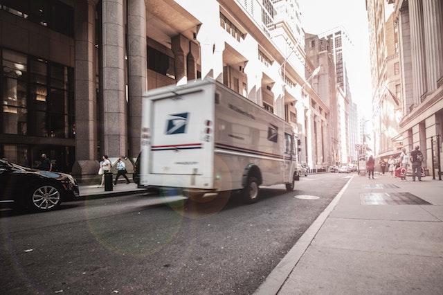USPS truck driving through city