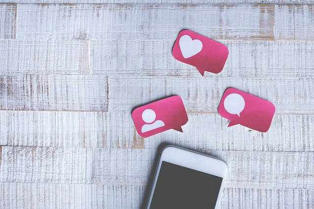 White cell phone with images of likes hearts and comments]