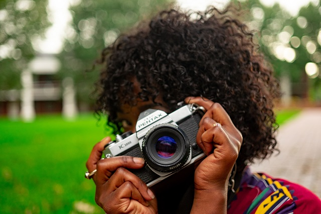 Woman holding camera taking pictures