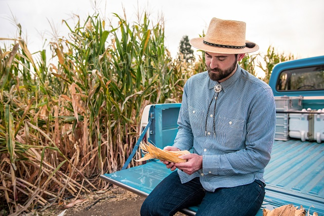 Evan Rocheford inspecting Orange Corn