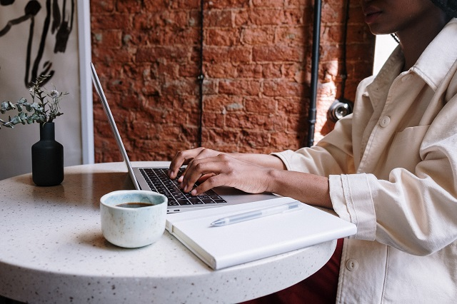 Woman typing on laptop with coffee and notepad nearby