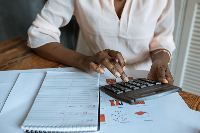 Woman using calculator at desk