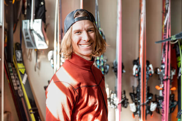 Mattias Giraud smiling in front of skis