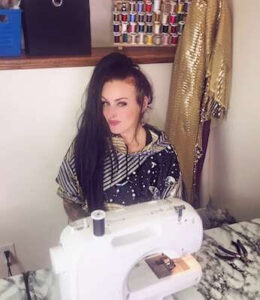Kelly sitting at sewing machine