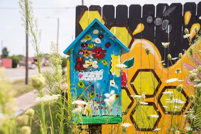 A colorfully painted beehive in front of a fence with a black and yellow honeycomb design
