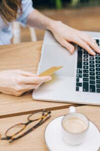 Person holding a credit card while working on laptop