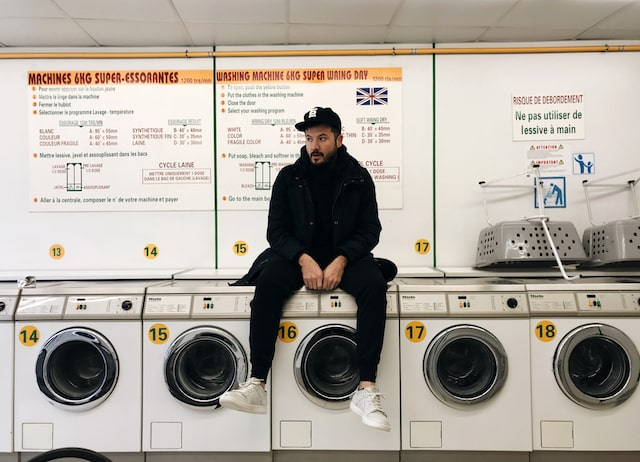 SYML Brian Fennell Sitting on Washing Machine in Laundromat
