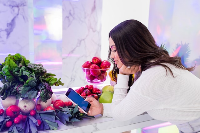 Ayesha Curry Looking into Smartphone with Vegetables on Counter