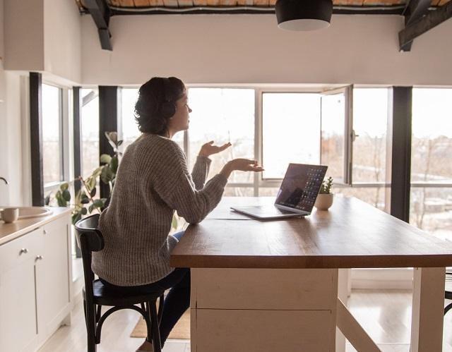 Woman Wearing Headphones Having Conversation On Laptop