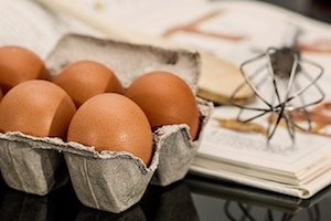 Eggs And Whisk And Cookbook In Background