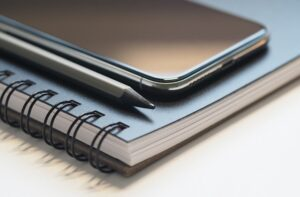 Mobile Phone Resting On A Notebook Illustrating Business Research
