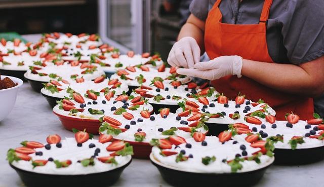 Worker Preparing Multiple Pies In Kitchen