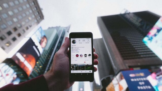 Holding Mobile Phone with Instagram on Screen in City