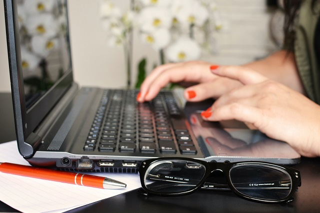 Woman Typing On Laptop Illustrating How To Start A Makeup Blog