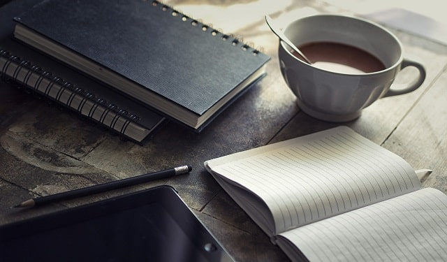 Open Notebook With Tablet and Coffee Nearby