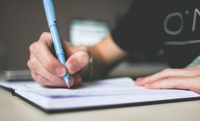 Person Making A List Illustrating Keyword Domain Name Audit