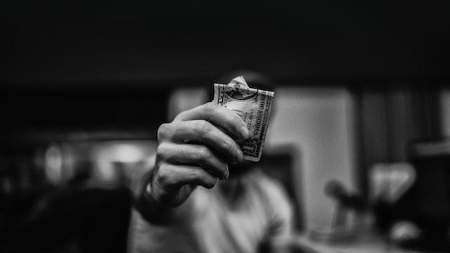Man Holding Dollar Bill Represents Paid Social Advertising