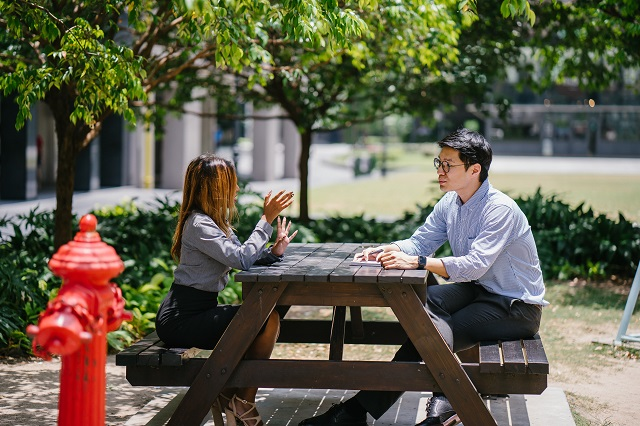Two People Having A Discussion At A Picnic Bench
