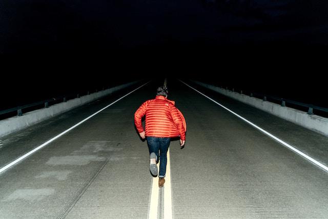 Man running down road a night