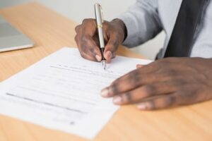 Business Filings Black Man Signing Document