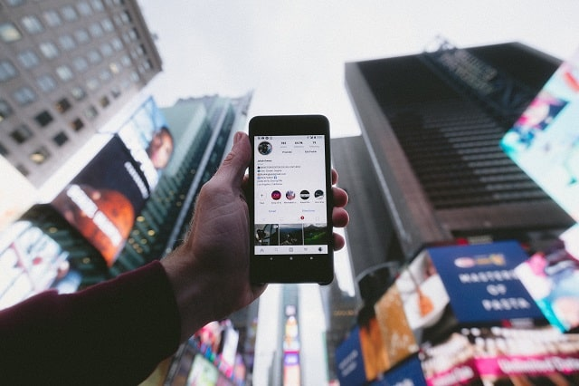Smartphone With Instagram Page With Cityscape In Background