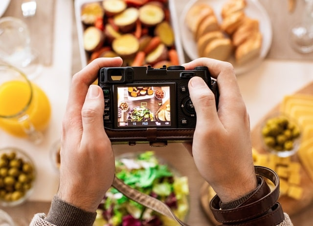 Person Taking A Photo Of Meal On Table