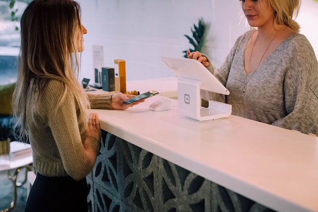 Two Women At Retail Shop Counter