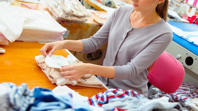 Woman Folding Clothing to Ship Represents Retail Inventory Management