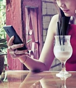Woman on Smartphone with Cocktail